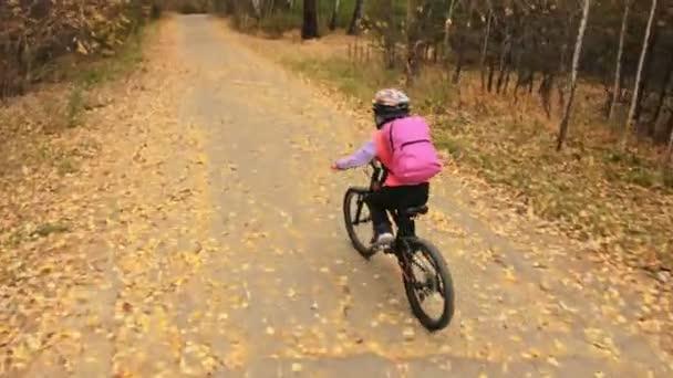 Egy kaukázusi gyerekek lovagolni kerékpár út őszi parkban. Kis lány lovaglás fekete narancssárga ciklus erdőben. Gyerek megy kerékpáros sport. Motoros mozgás lovagolni a hátizsák és a sisak. Mountain bike kemény farok.