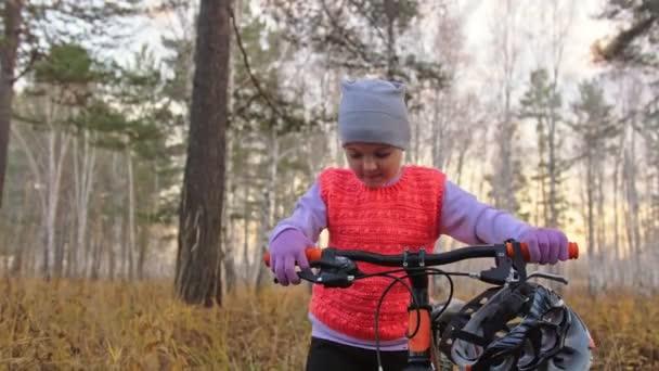 Egy kaukázusi gyermekek séta, kerékpár, őszi parkban. Kislány fekete narancssárga ciklus séta erdőben. Gyerek megy kerékpáros sport. Motoros mozgás lovagolni a hátizsák és a sisak. Mountain bike kemény farok.
