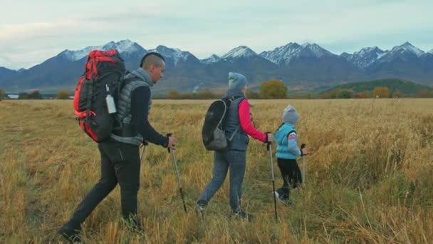 People walk near beautiful mountains in wheat field. Family travels. People environment by mountains. Parents and kid walk using trekking poles. Man and woman have hiking backpacks, flasks, mugs.