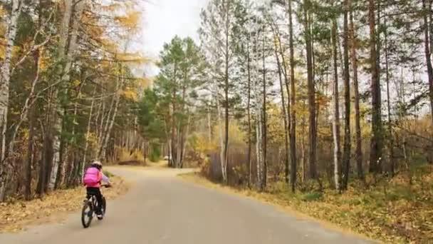 Jeden bělošský děti jezdí na kole silnice v podzimním parku. Malá dívka na koni černý oranžový cyklu v lese. Chlapče jde cyklistické sporty. Biker pohybu jezdit s batohem a helmu. Horské kolo tvrdý ocas.