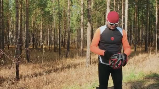 Training an athlete on the roller skaters. Biathlon ride on the roller skis with ski poles, in the helmet. Autumn workout. Roller sport. Adult man riding on skates. Athlete puts on skis and helmet.