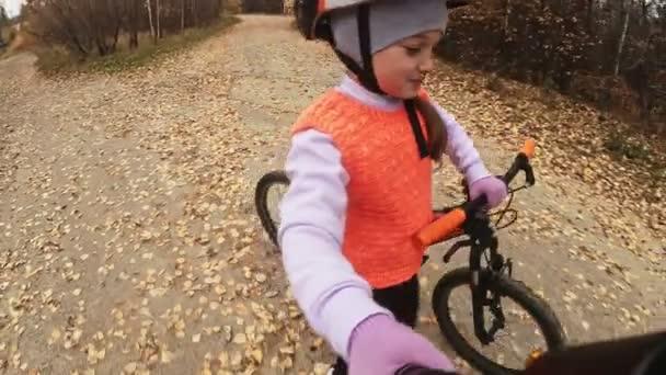 Ein kaukasisches Kind fährt Fahrradstraße im Herbstpark. kleines Mädchen, das im Wald auf einem orangefarbenen Fahrrad fährt. Kind fährt Fahrradsport. Fahrradtour mit Rucksack und Helm. Mountainbike-Hardtail.