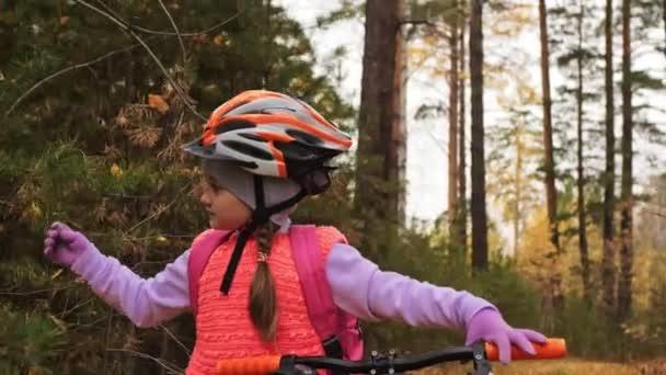 Jeden bělošský děti chodit s kolo v podzimním parku. Malá holčička vycházkové černé oranžové cyklu v lese. Chlapče jde cyklistické sporty. Biker pohybu jezdit s batohem a helmu. Horské kolo tvrdý ocas.