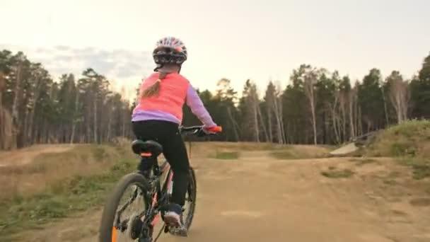 Jeden bělošský děti jezdí na kole silniční trati v dirt parku. Dívka na koni černý oranžový cyklu v dráze. Chlapče jde cyklistické sporty. Biker pohybu jezdit s batohem a helmu. Horská kola hardtail