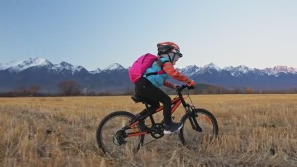 Jedno kolo jízd na kavkazské děti v pšeničné pole. Malá dívka na koni černý oranžový cyklu na pozadí krásných zasněžených hor. Biker pohybu jezdit s batohem a helmu. Horská kola hardtail.