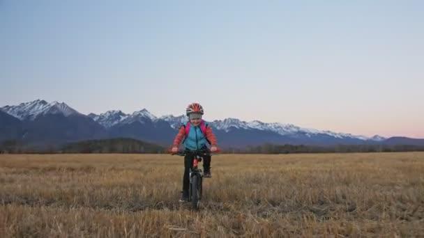Jedno kolo jízd na kavkazské děti v pšeničné pole. Malá dívka na koni černý oranžový cyklu na pozadí krásných zasněžených hor. Biker pohybu jezdit s batohem a helmu. Horské kolo tvrdý ocas.
