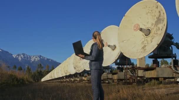 Žena student operátor ze sluneční pozemské Fyzikální ústav sleduje komunikačních zařízení v poznámkovém bloku. Jedinečné pole sluneční radioteleskopu. Solární rádio dalekohledem. Satelitní antény v horách.