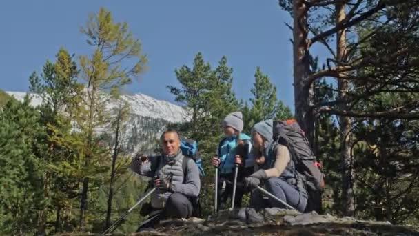 Család utazik. Emberek környezet hegyek, folyók, patakok. A szülők és a gyerekek séta, trekking gyalogoltunk. Férfi és nő van szakmai túrázás hátizsákok, lombikok, bögréket és egyéb berendezések.