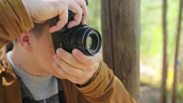Turistické fotografování rozhledů v lese podle hory. Muž, Střelba malebný výhled. Guy má foto a video na staré retro fotoaparát na film. Profesionální fotograf, cestovatel.