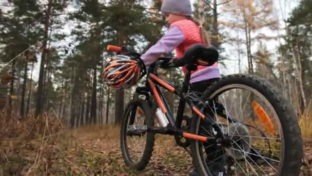 One caucasian children walk with bike in autumn park. Little girl walking black orange cycle in forest. Kid goes do bicycle sports. Biker motion ride with backpack and helmet. Mountain bike hard tail.