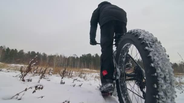 Profesionální sportovec extrémní biker jezdecké tuku kolo v přírodě. Cyklista jezdit v zimě sněhové pole, lesa. Muž trik na horské kolo s velkými pneumatiky v kopím a štítem. Zpomalený pohyb 180fps