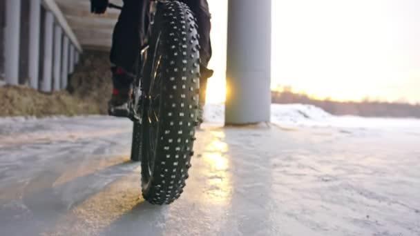 Profesionální sportovec extrémní biker jezdecké tuku kolo v přírodě. Pohled na detail zadního kola. Cyklisté jezdí v zimním lese. Muž na horské kolo s velkými pneumatiky. Sníh letět do objektivu fotoaparátu