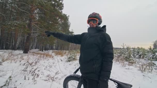 Profesionální sportovec extrémní biker stát fat bike v přírodě. Cyklista sklopit v zimním lese sněhu. Muž chůze s horské kolo s velkými pneumatiky v helmu a brýle. Zpomalený pohyb v 180fps