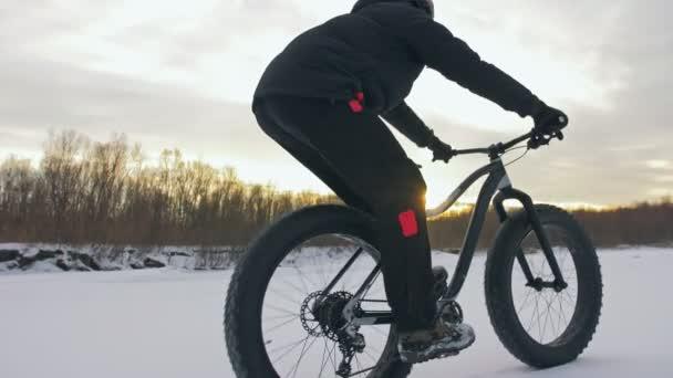 Profesionální sportovec extrémní biker jezdecké tuku kolo v venkovní. Cyklisté jezdí v zimě sníh lese. Člověk dělá zkušební trik bunny hop skok na horské kolo s velkými pneumatiky v helmy a brýle.