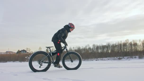 Professional extreme sportsman biker riding a fat bike in outdoors. Cyclist ride in the winter on snow ice. Man does trick on a mountain bicycle with big tire in helmet, glasses. Slow motion 180fps.