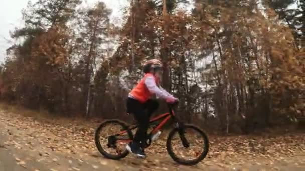 Jeden bělošský děti jezdí na kole silnice v podzimním parku. Malá dívka na koni černý oranžový cyklu v lese. Chlapče jde cyklistické sporty. Biker pohybu jezdit s batohem a helmu. Horské kolo tvrdý ocas