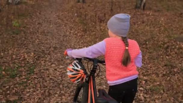 Jeden bělošský děti chodit s kolo v podzimním parku. Malá holčička vycházkové černé oranžové cyklu v lese. Chlapče jde cyklistické sporty. Biker pohybu jezdit s batohem a helmu. Horská kola hardtail
