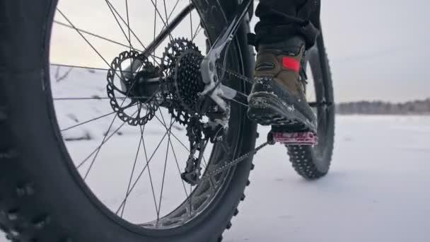 Profi extrém sportoló motoros lovaglás kövér kerékpár a szabadban. Kerékpáros téli hó erdő lovagolni. Ember csinál próba fogás Gurítás a hegyi kerékpár és nagy abroncsgyártó sisak és szemüveg.