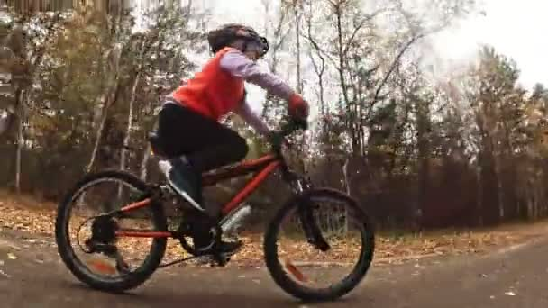 One caucasian children rides bike road in autumn park. Little girl riding black orange cycle in forest. Kid goes do bicycle sports. Biker motion ride with backpack and helmet. Mountain bike hard tail.