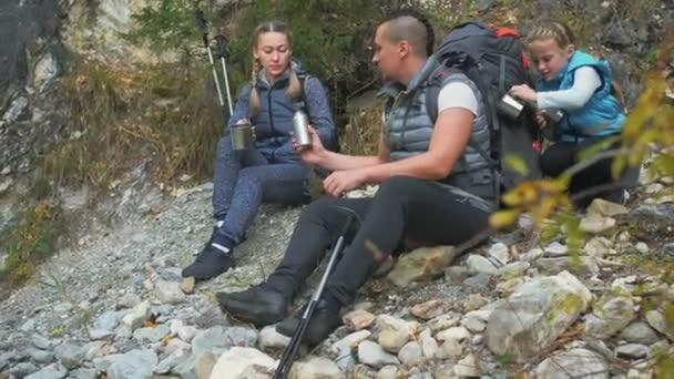 Pihenés és ital tea a hegyi folyó közelében. Család utazik. Emberek környezet hegyek, folyók, patakok. A szülők és a gyerekek séta, trekking gyalogoltunk. Férfi és nő van, túrázás hátizsákok.