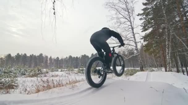 Profesionální sportovec extrémní biker jezdecké tuku kolo v přírodě. Cyklisté jezdí v zimě sníh lese. Člověk dělá zkušební trik wheelie na horské kolo s velkými pneumatiky v helmy a brýle
