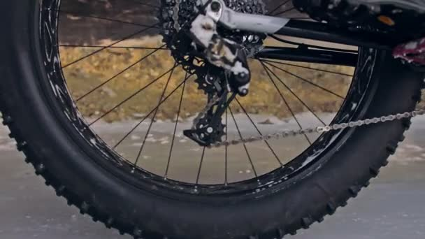 Professional extreme sportsman biker riding fat bike in outdoor. Close-up view of rear wheel. Cyclist ride in winter forest. Man on mountain bicycle with big tire. Snow fly into the lens camera.