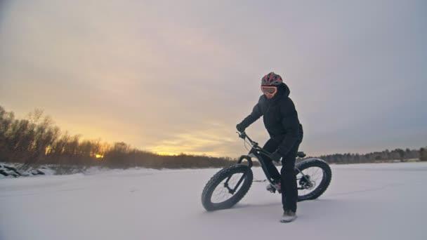 Profesionální sportovec extrémní biker jezdecké tuku kolo v přírodě. Cyklisté jezdí v zimě sníh lese. Muž zkušební trik kolo Převrátit Skok na horské kolo s velkými pneumatiky v helmu a brýle