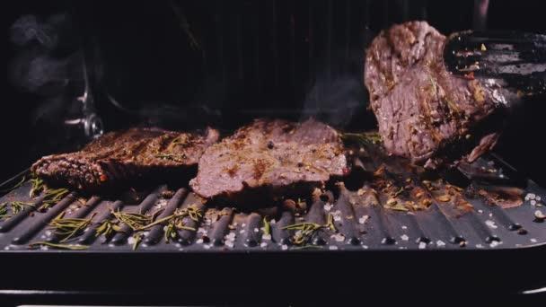 Lahodný šťavnatý masový steak na grilu. Zrající prvotřídní pečené hovězí na mramoru. Elektrická pečeně, rozmarýn, černý pepř, sůl. Kuchyňské kleště.