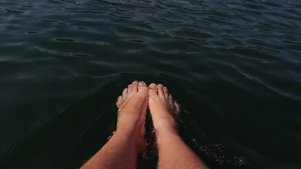 Naked hairy male legs hang from a catamaran. The legs of a man swim towards the waves on a ship. First person of view from the boat.