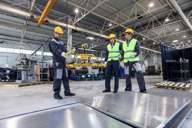 Workers standing near aluminium billets at CNC machine shop stock vector