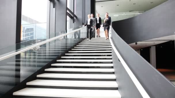 Group of business people walking and taking at stairs in an office building