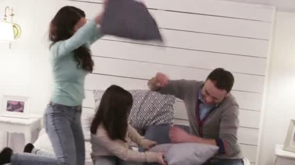 Az emberek, a járműcsalád-koncepció - a boldog gyermek szüleivel, miután párna küzdelem az ágyban otthon