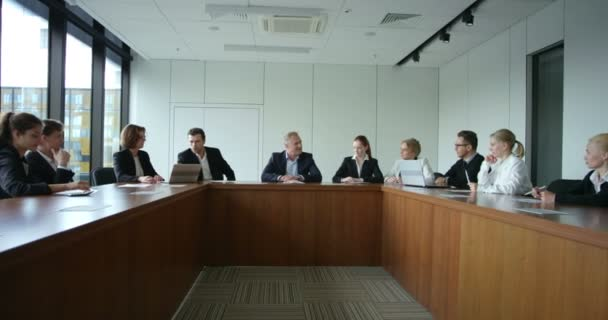 Business People at corporate meeting sitting around table and talking