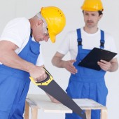 Worker works with handsaw, foreman on background