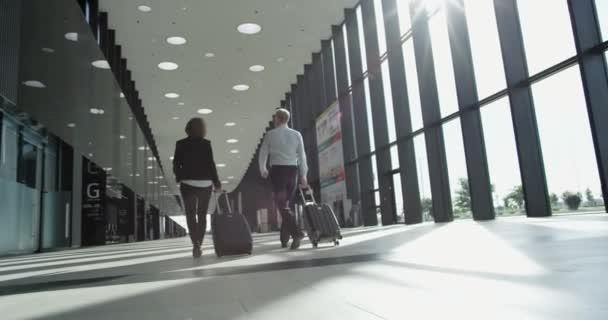 Podnikatelé ve formálním oblečení chůzi v letištní terminál s kufry