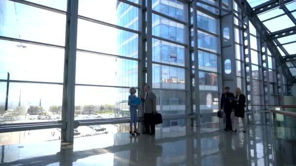 Geschäftsleute gehen in moderne gläserne Bürogebäude-Lobby