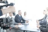 Videograf mit Schwebestativ, macht Video von Geschäftsleuten bei Besprechungen