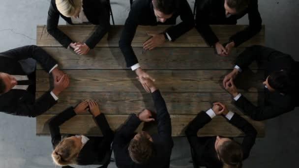 Geschäftsleute sitzen am Tisch und reden, schütteln Hände, halten die Fäuste