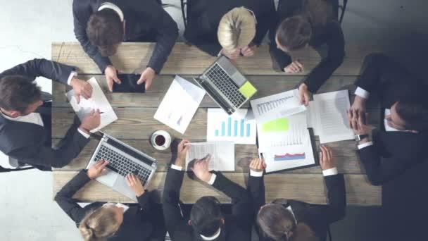 Obchodní lidé, kteří spolupracují při analýze finančních dokumentů s příjmem, grafy a grafy, koncepce týmové práce