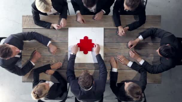 Business people putting last piece of puzzle on wooden table, teamwork and problem solution concept , clapping hands