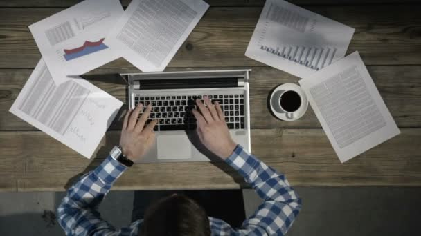 Muž, který sedí u stolu před laptopem, pracuje s finančními dokumenty a hledí na Náramkové hodinky, dokončovací práce před termínem, konec pracovního dne