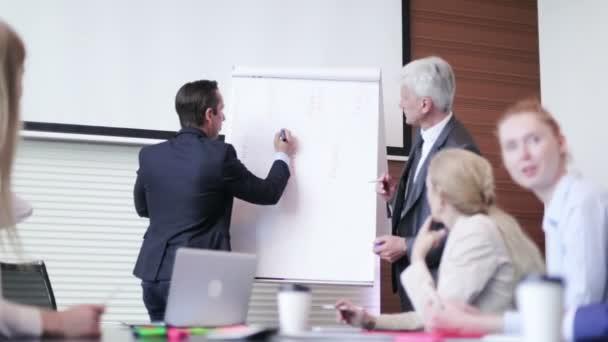 Obchodní muž hovořící o semináři na tabuli nebo flipchart