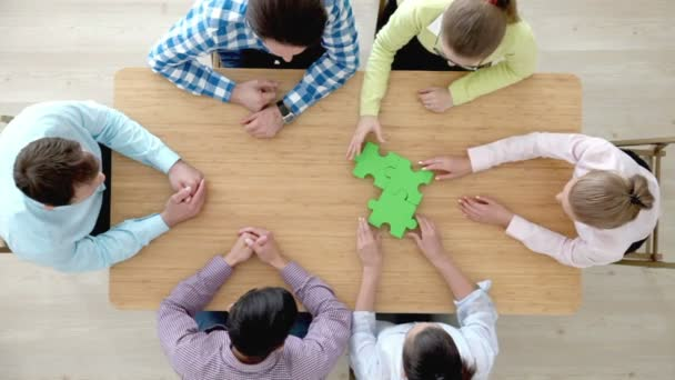 Businesspeople assembling jigsaw puzzle , then applauding , problem solution teamwork concept