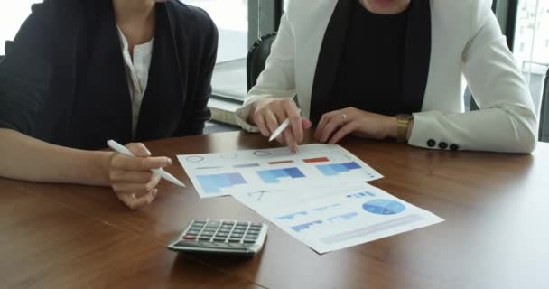 Business women pointing at diagrams discussing financial reports at workplace