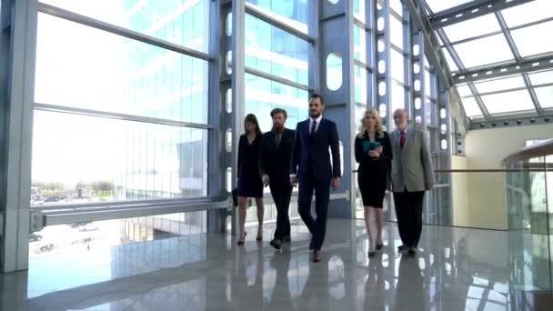 Üzletcsoport-csapat a folyosón a hivatalban együtt
