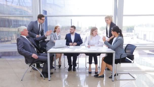 Business team sitting by the table with laptop and documents in office