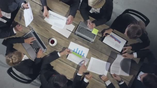 Gruppe verschiedener Führungskräfte, die sich an einem Tisch treffen und über Diagramme diskutieren, die statistische Datenanalyse zeigen