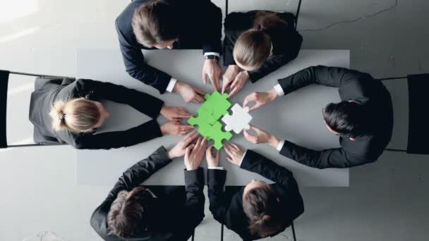 Obchodní lidé a skládačka na stole, koncepce týmové práce
