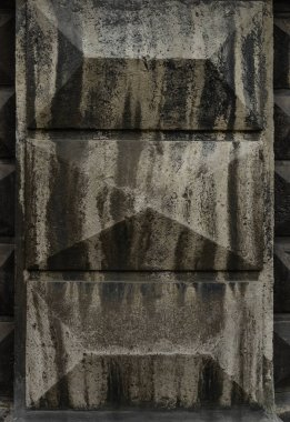 Reliefs on the concrete wall. In dark colors.