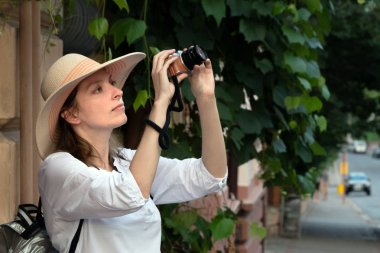 A woman in a hat and a white sweatshirt with a backpack travels and takes a photos. Tourist with vintage photo camera shooting on the street.